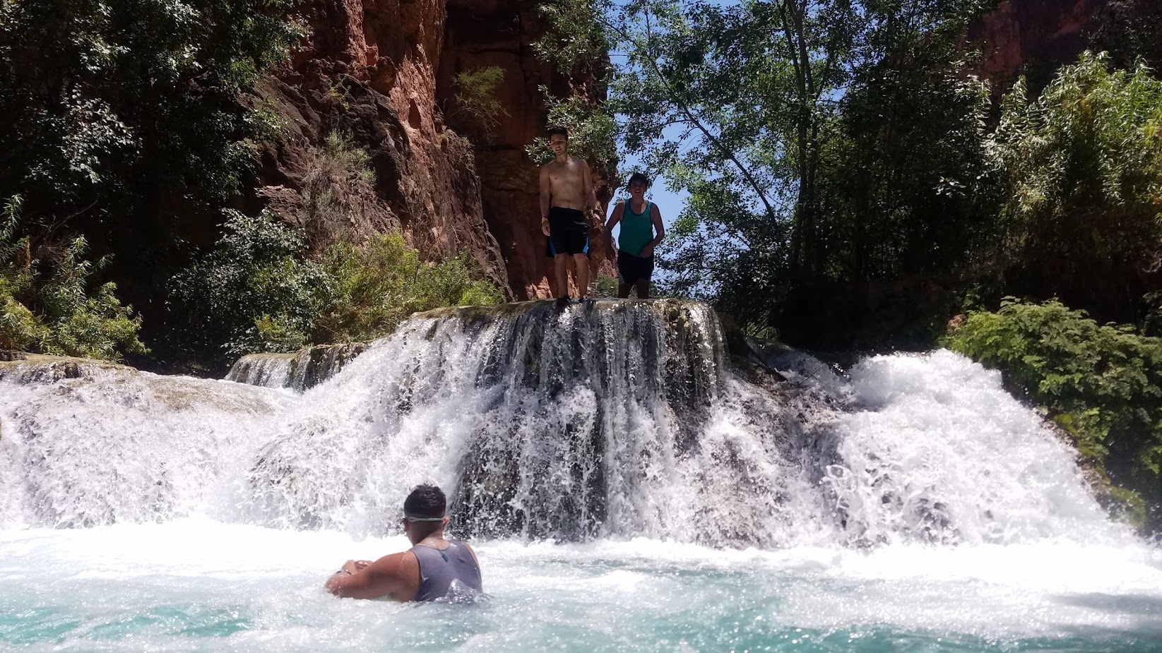 Swimming under 1 of many waterfalls