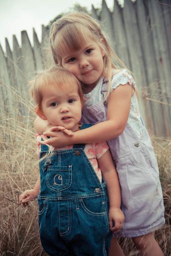 siblings hugging outside