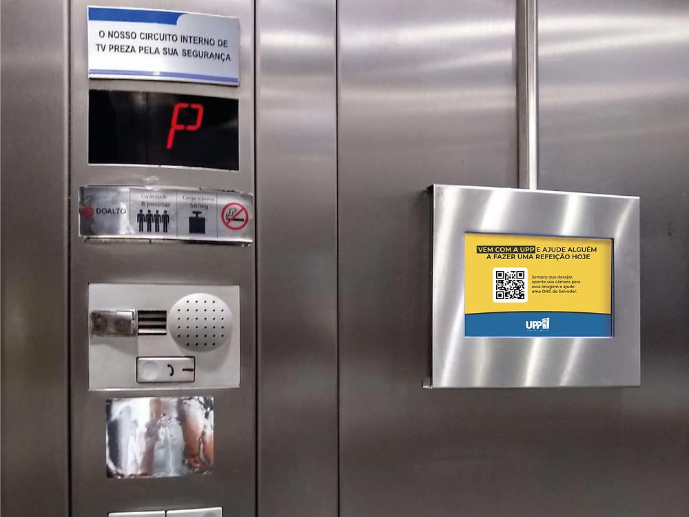A imagem mostra um pequeno televisor preso em uma das faces internas de um elevador em prédio residencial. Na tela está o código para doação solidária.