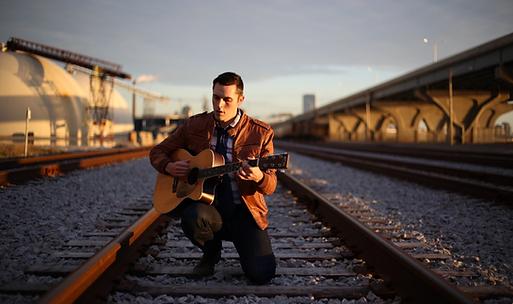 guitar player train tracks