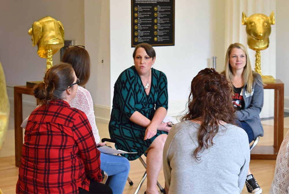 A group of women sit in a circle in a museum