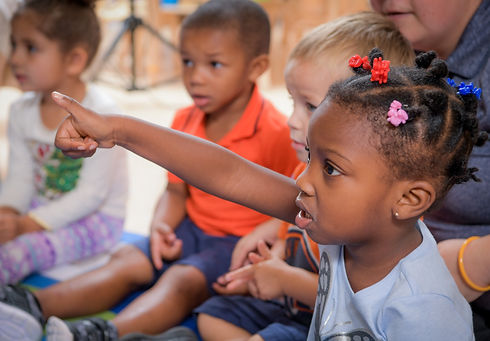A group of preschool aged children sit together. One holds her hand up, thumb raised