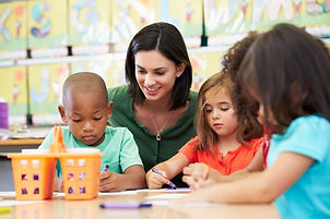 A young woman sits at a classroom table with preschool children.