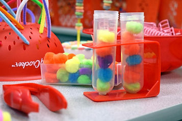 Fine motor skill activities including tongs, pompoms, and a colander threaded with pipe cleaners.