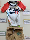 A display showing children's play clothes and the activities that the child was doing.