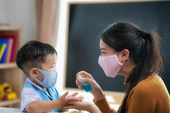 A teacher wearing a mask sprays hand sanitizer on the hands of a young child.