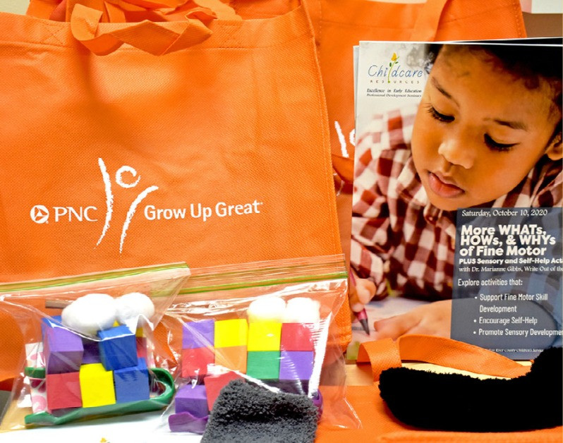 This photo shows orange bags with the PNC Grow Up Great logo, ziploc bags filled with blocks and cotton balls, and a paper handout.