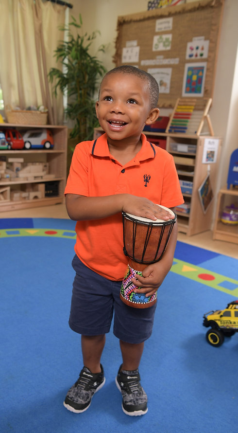 A boy stands in a classroom holding a drum