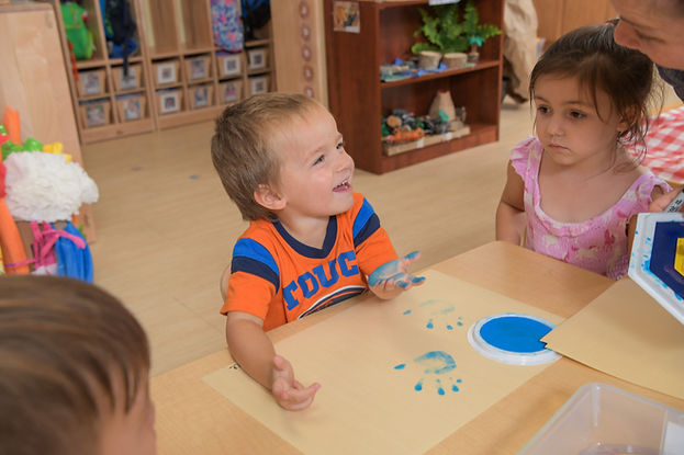 Children sit at a table, fingerpainting with blue paint