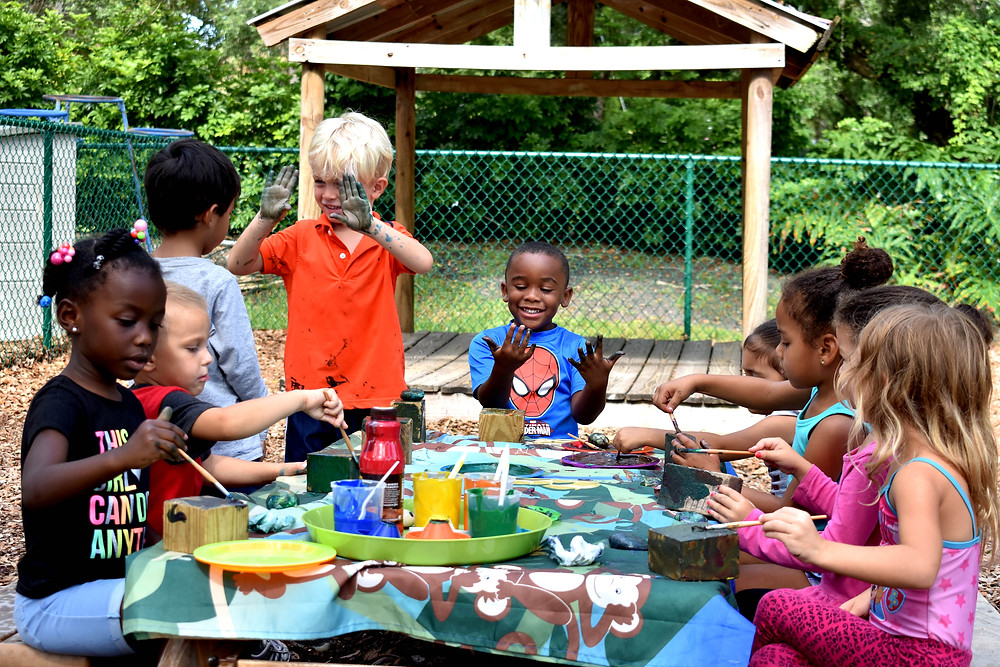 A group of preschools paints sitting at a picnic table in a playground.