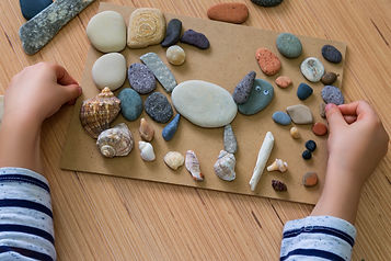 A child's hand holds rocks over more rocks spread out on construction paper.