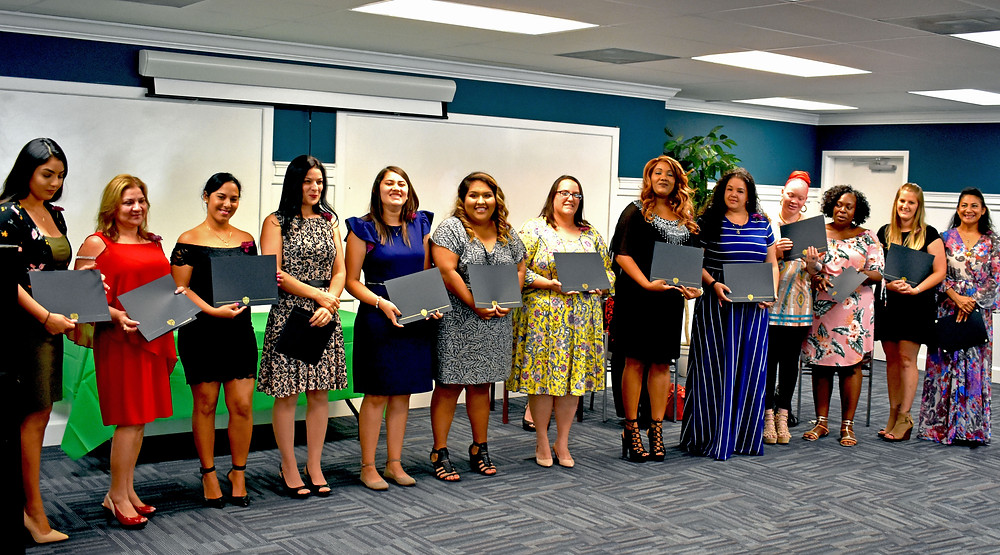 A group of women stand at the front of the room, holding graduation certificates.