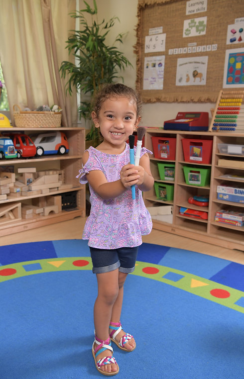 A girl stands in a classroom, holding paintbrushes and smiling at the camera