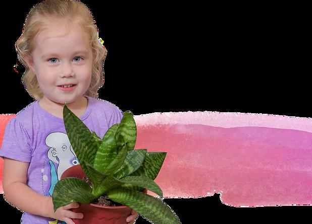 A preschool-aged girl holds a plant