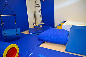 A room filled with blue physical therapy equipment, like a swing, a tunnel, and a ball pit