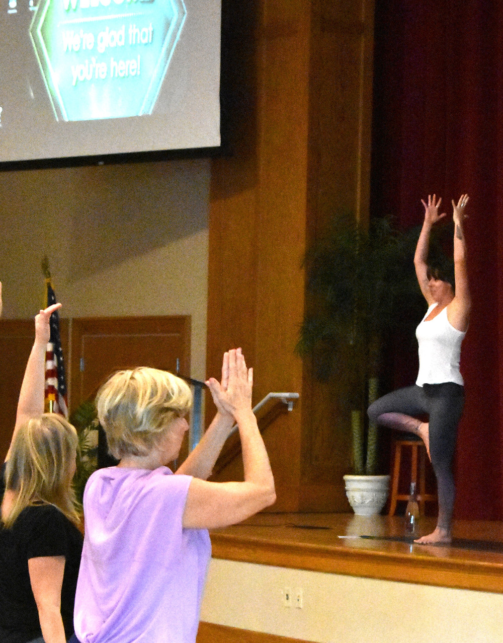 A woman stands on stage, leading a yoga class.