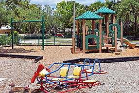 A playground with a swing set and jungle gym