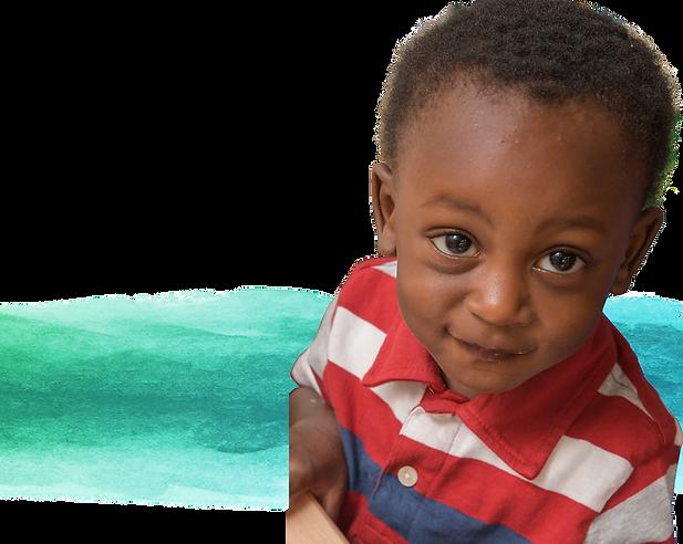A preschool-aged boy smiles at the camera