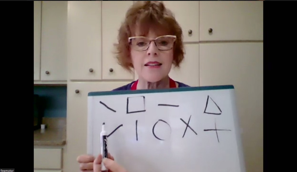 A woman holds a whiteboard and a marker. The whiteboard is covered with lines, shapes, and crosses.