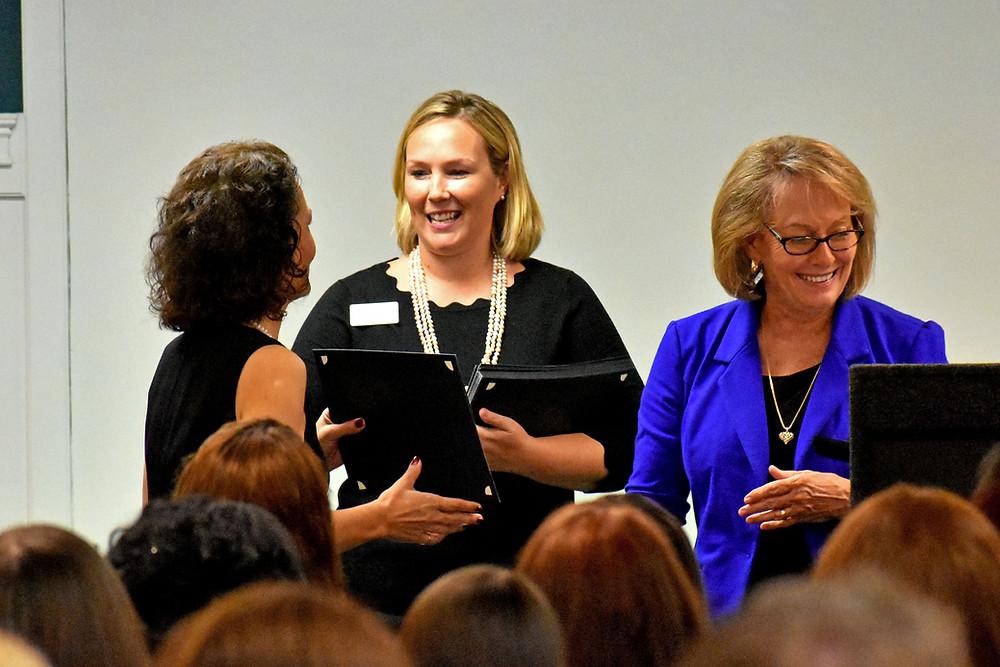 A woman receives a professional certificate.