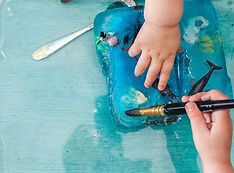 Children play with a block of ice using their hands and a paintbrush
