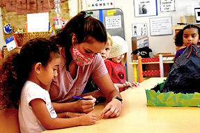 A woman sits next to a preschooler. The woman is writing