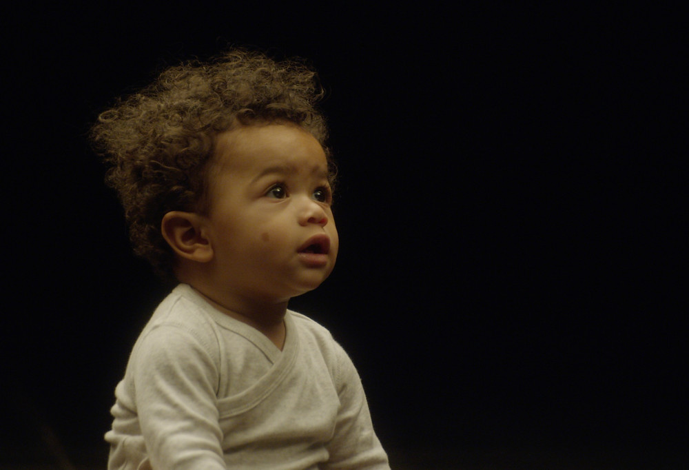 A baby sits in front of a black background