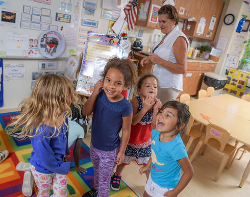 Children and their teacher stand in a classroom