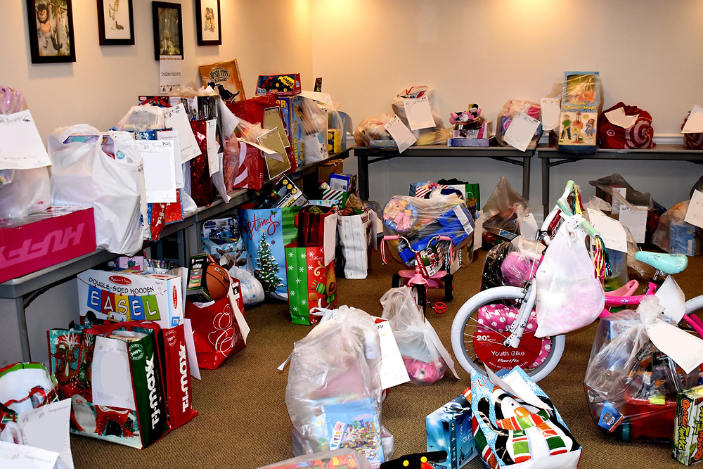 Gift bags and assorted toys, including bikes and dolls, line tables and the floor in a conference room.