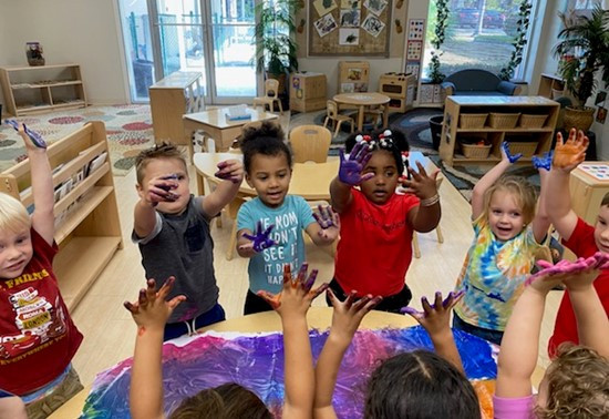 A group of preschoolers stand around a table holding their hands in the air. Their hands are covered in bright paint.
