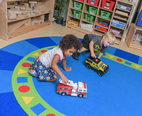 A preschool boy and girl sit on a blue carpet, playing with toy trucks
