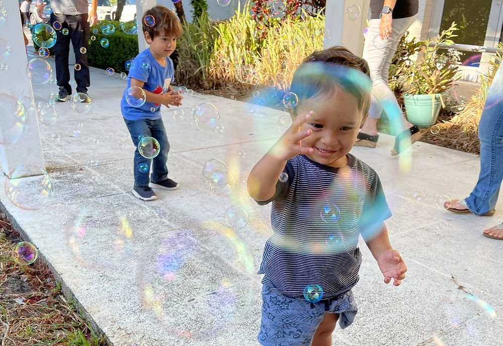 Two boys stand on a sidewalk, playing with bubbles.