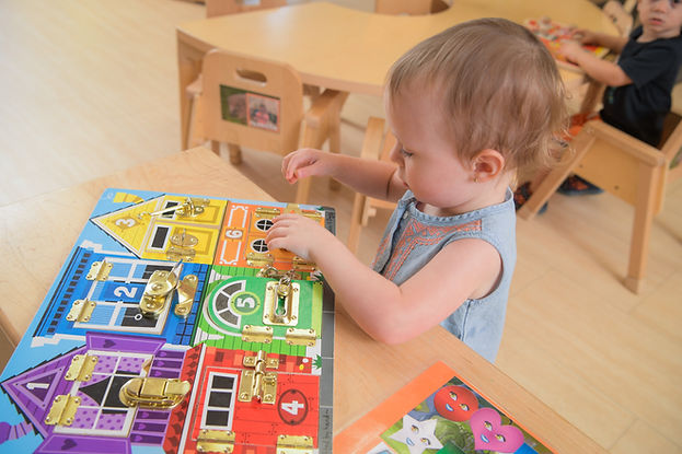 A young child sits a table in a classroom, completing a puzzle