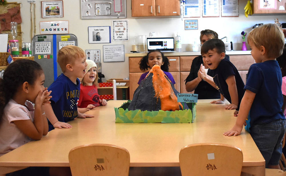 A group of preschool students gather around a table. On the table is a papier-mache volcano.