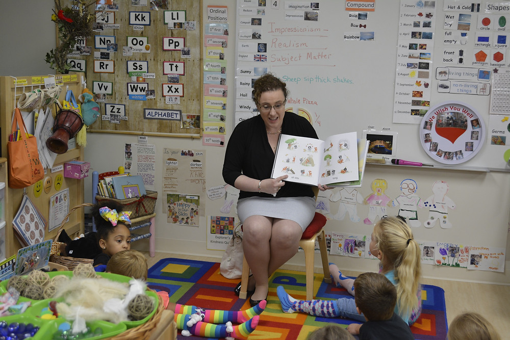 A seated woman reads a picture book to a group of preschoolers in a classroom.