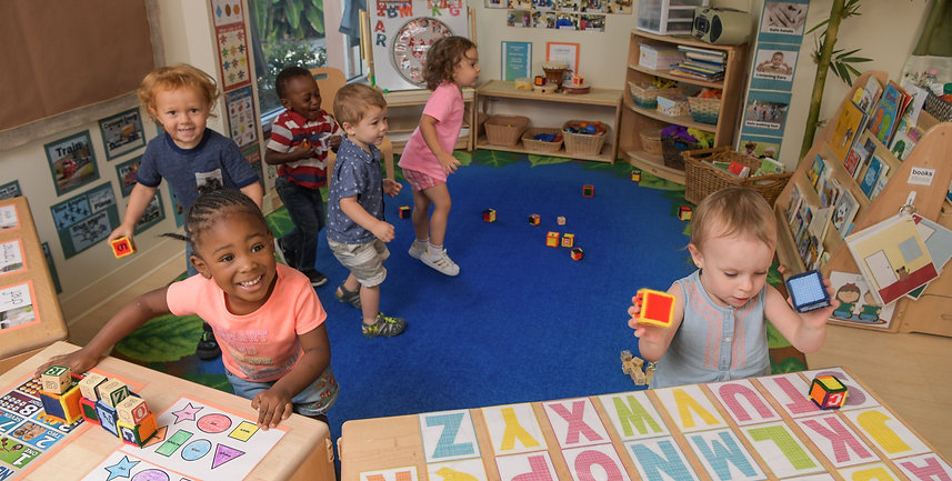 Children stand in a classroom with a blue rug. Blocks are on the floor