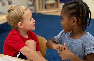 Two children sit next to each other at a table.