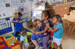 A group of children stand in a classroom hugging each other.