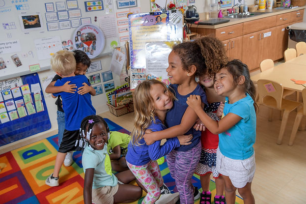 Children stand in a group, hugging, in a classroom