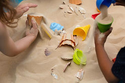 Children play in sand with shells and plastic toys
