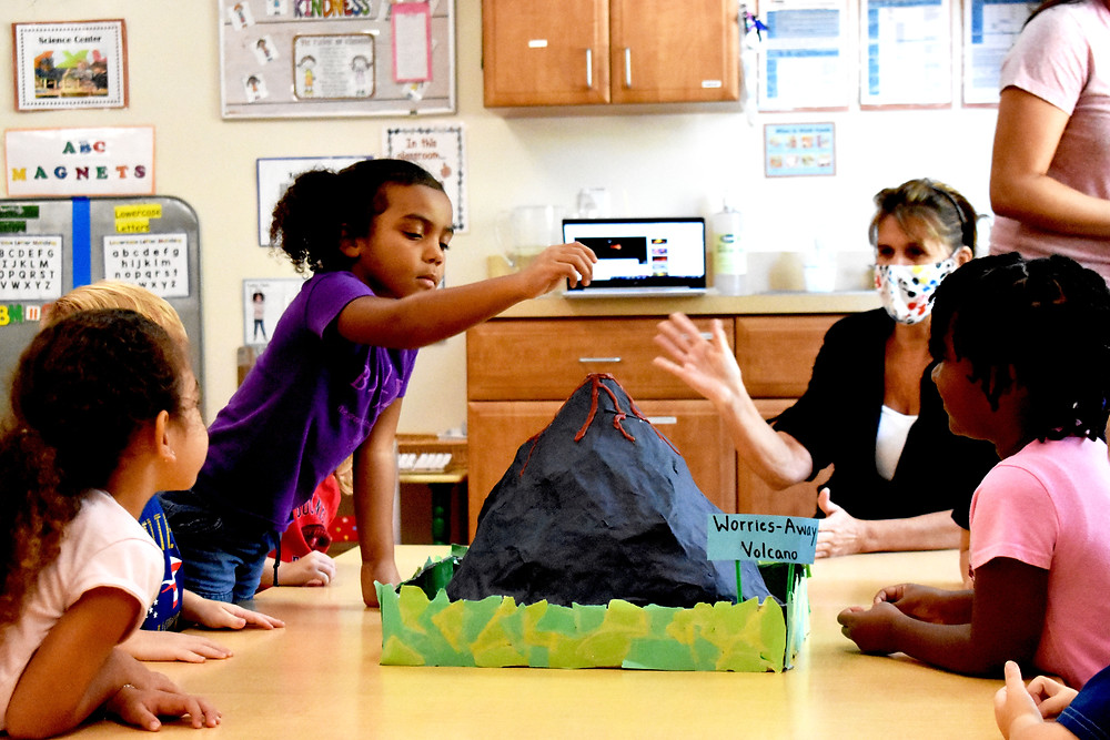 Preschool students and their teacher sit at a table. On the table is a papier-mache volcano. One student is standing, holding her hand above the volcano.