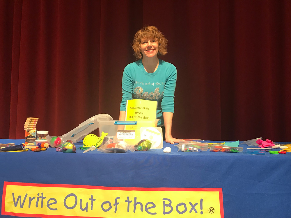 A woman stands behind a table covered in small toys, games, and writing implements.