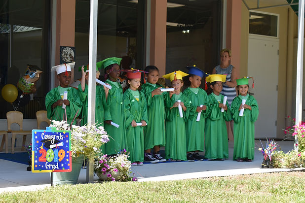 Preschool children in green graduation gowns and caps stand outside in front of a school.