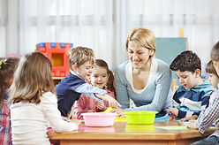 A teacher sits with preschool children at a table in a classroom.
