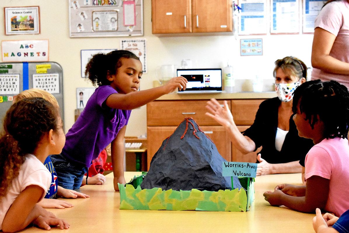 Preschoolers sit at a table with their teacher. On the table is a papier-mache volcano. One of the students stands with her hand raised over the volcano.