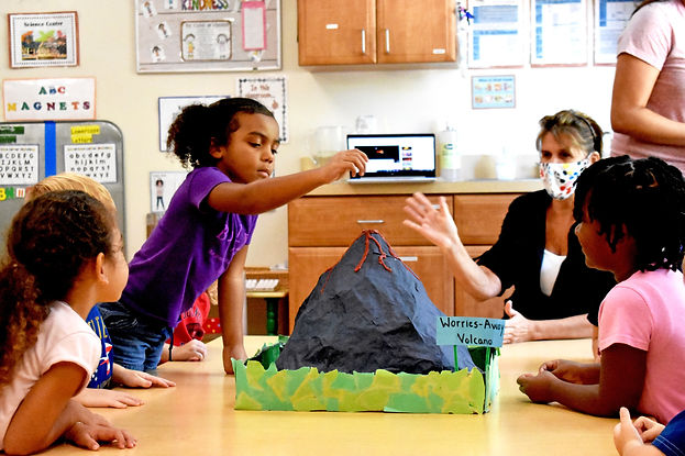 Children sit with their teacher at a table. On the table is a papier mache volcano. One child stands, hand raised over the volcano.
