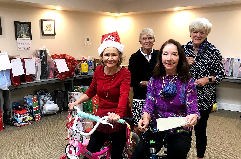 Four women smile at the camera, grouped together in a conference room surrounded by gifts. The two women in front are sitting on bicycles.