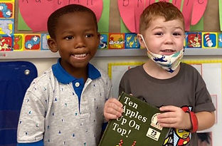 Two children stand in front of a bulletin board. One holds a book.