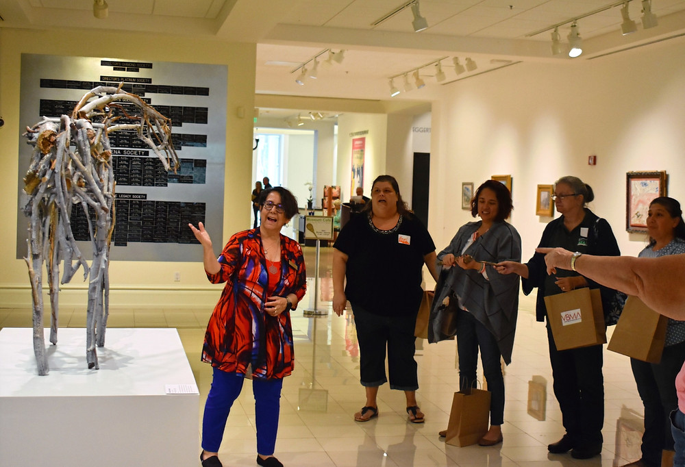 A group of women stand in front of a small sculpture of a horse.