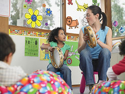 A young child and a teacher are sitting in a classroom. They are holding tambourines.